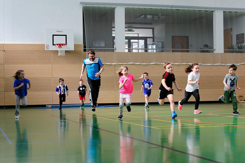 Bewegungsschule Kinder und Trainer laufen